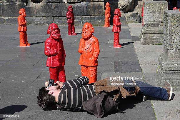 Visitors takes a photo of some of the 500 one meter tall statues of German political thinker Karl Marx on display on May 5 2013 in Trier Germany The...