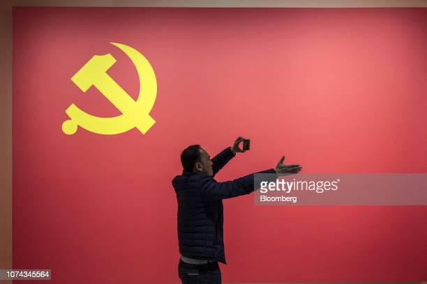 """Visitors takes a photograph in front of the Chinese Communist Party flag in the """"Great Tides Surge Along the Pearl River 40 Years of Reform and..."""