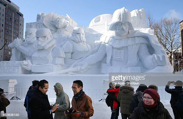 Visitors takes photographs in front of the snow statue of Darth Vader during the 66th Sapporo Snow Festival at Odori Park on February 6 2015 in...