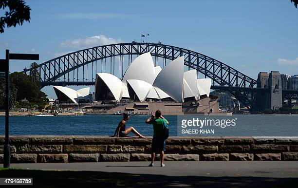 Visitors takes pictures in front of Sydney's iconic landmarks the Opera House and Harbour Bridge on March 19 2014 According to the Australian Bureau...