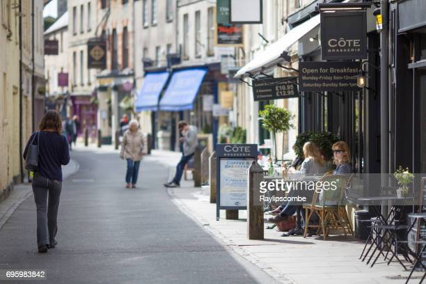visitors taking a welcome refreshment break in the cafes along black jack street in cirencester, england. - cirencester stock pictures, royalty-free photos & images