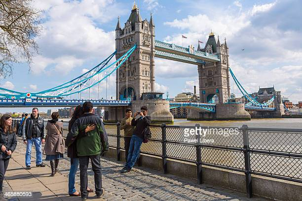 Visitors taking photographs at the Tower of London with Tower Bridge in the background