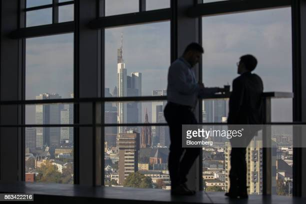 Visitors talk as skyscrapers tower over commercial and residential property on the city skyline as seen from the 15th floor pantry area inside the...