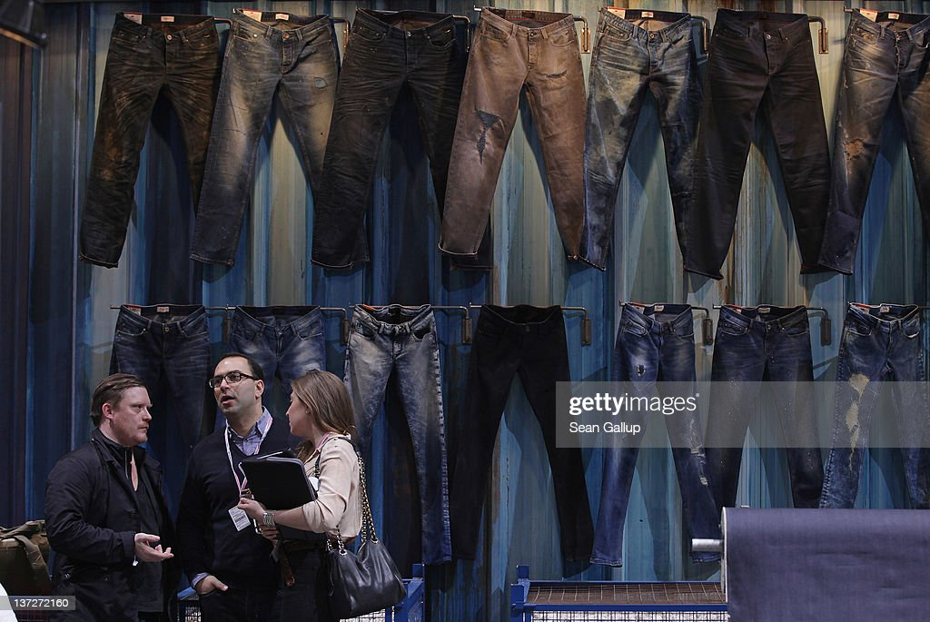 Visitors talk next to a wall of denim jeans at a stand at the 2012 Winter Bread And Butter fashion trade fair at former Tempelhof Airport on January 18, 2012 in Berlin, Germany. Bread And Butter is a semi-annual event and is among Europe's major fashion trade fairs.
