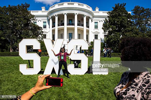 Visitors talk photos on the South Lawn of the White House during the 'South By South Lawn' SXSL festival on October 3 2016 in Washington DC The White...