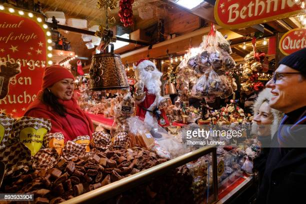 Visitors talk with a Christmas market shop assistent at the annual Christmas market at Roemerberg on December 16 2017 in Frankfurt Germany Christmas...