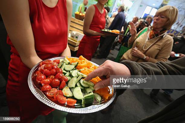 Visitors taste vegetables from Holland including cucumber tomatoes and paprikas at the 2013 Gruene Woche agricultural trade fair on January 18 2013...