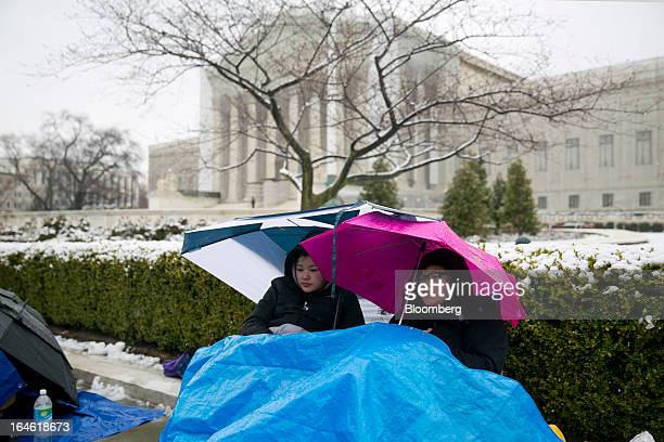Visitors Taylor Carter right and Talia Carter sit underneath umbrellas and a tarp while in line outside the Supreme Court building in Washington DC...