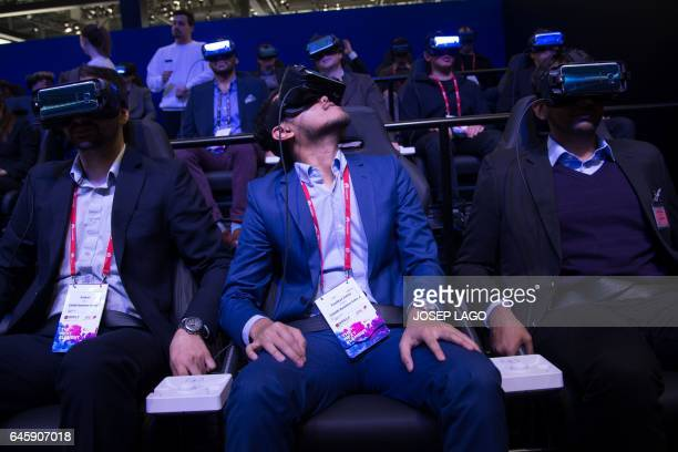 Visitors test the 'Gear VR 4D' device at the Samsung stand on the first day of the Mobile World Congress in Barcelonaon on February 27 2017 in...
