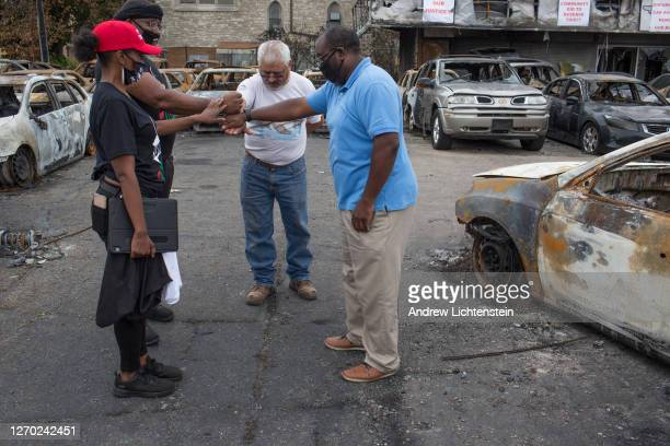Visitors to a car dealership burned in last week's riots hold a short prayer on September 1 in Kenosha Wisconsin President Trump came to tour...