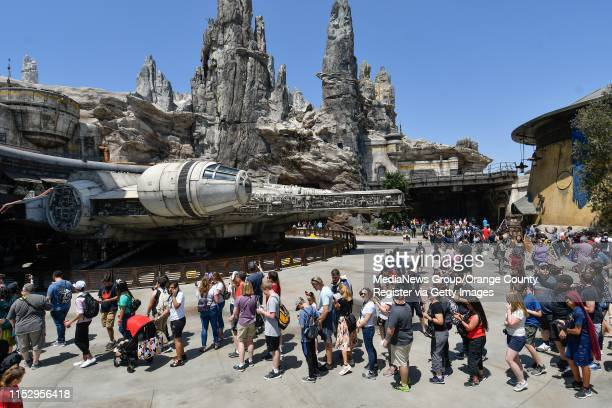 """Visitors to Black Spire Outpost wait in line for the Millennium Falcon: Smugglers Run ride on opening day at Star Wars: Galaxy""""u2019s Edge at..."""