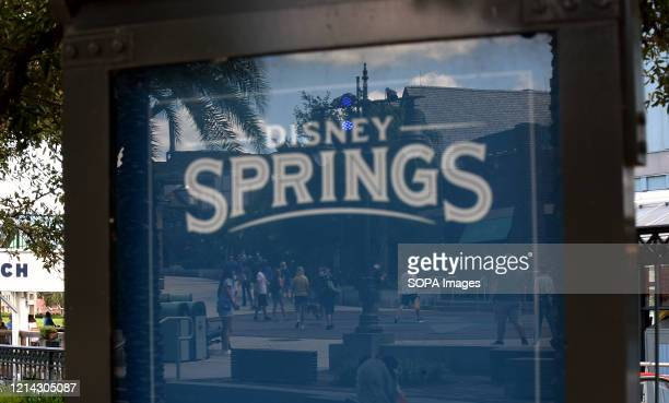 Visitors to Disney Springs at Walt Disney World are seen in a reflection on the day the retail dining and entertainment complex begins a phased...