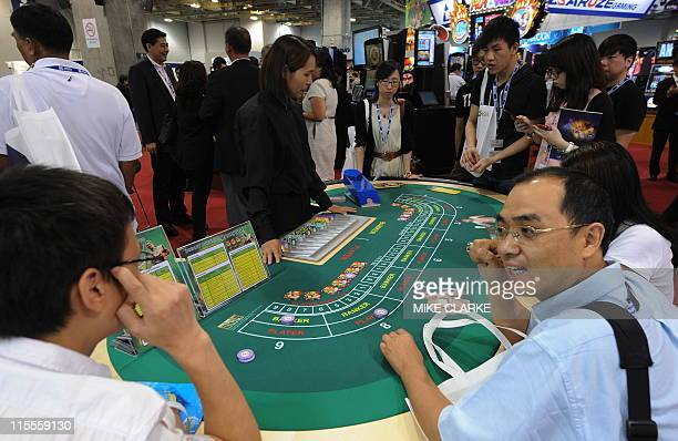 Visitors to Global Gaming Expo check out the latest gambling tables at a gaming exhibition in Macau on June 8 2011 Global Gaming Expo Asia a gaming...