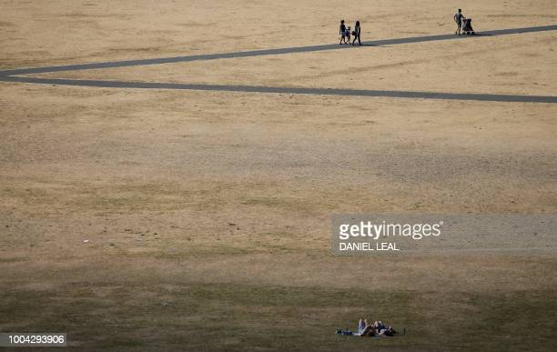 TOPSHOT Visitors to Greenwich Park walk on the footpaths in between the dry brown grass in London on July 23 2018 Wildfires in the Arctic Circle...