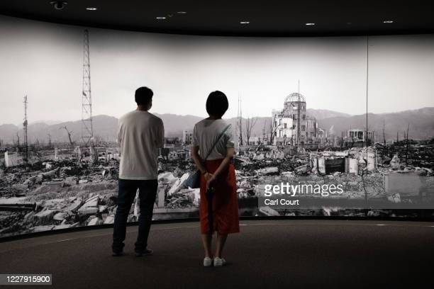 Visitors to Hiroshima Peace Memorial Museum view a large scale panoramic photograph of the aftermath of the atomic bomb attack on Hiroshima on August...