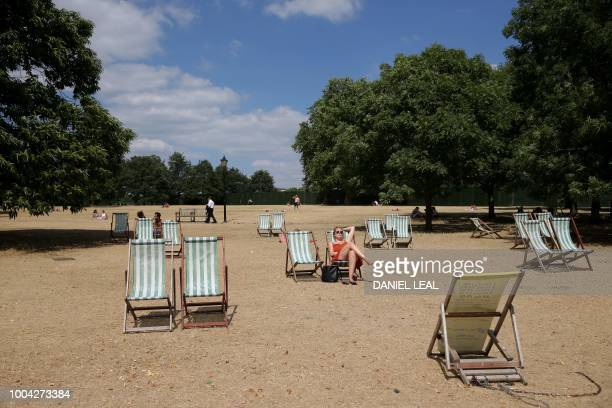 Visitors to Hyde Park sit on deck chairs on the dry brown grass in London on July 23 2018 Wildfires in the Arctic Circle droughtstricken farmers and...