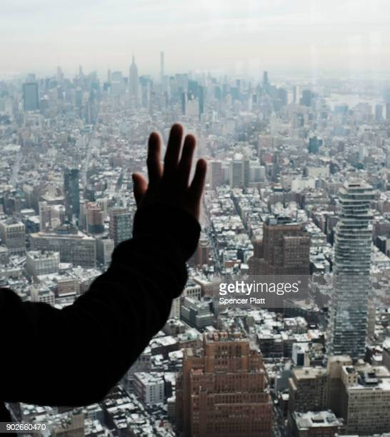 Visitors to One World Observatory look out at a snow covered Manhattan on January 8 2018 in New York City Following a week of snow and record...