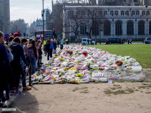 Visitors to Parliament Square Garden in London where floral tributes have been left for victims of the terror attack in Westminster Several people...