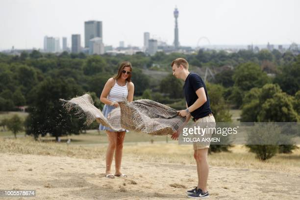 Visitors to Primrose Hill shake a blanket after sitting on the dry brown grass in London on July 26, 2018. - Britain has been in the grip of its...
