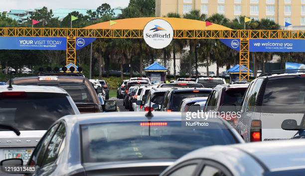 Visitors to SeaWorld Orlando are seen at the theme park's entrance as the attraction reopens after closing in March due to the coronavirus pandemic...