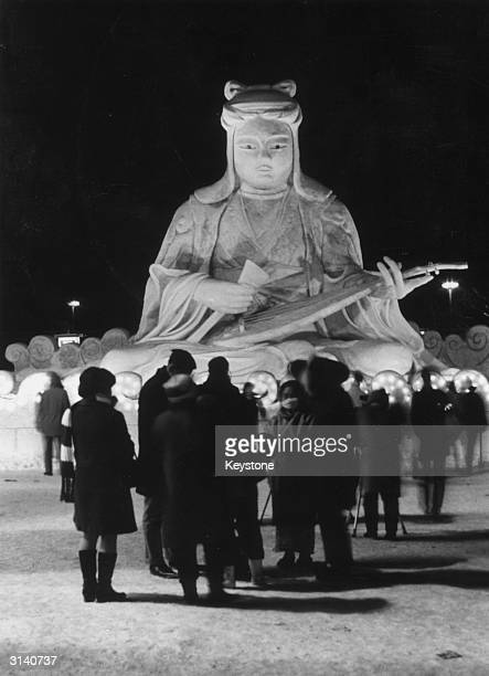 Visitors to the 22nd Sapporo Snow Festival on the island of Hokkaido in Japan admiring an ice statue of Benten a goddess of luck music eloquence art...