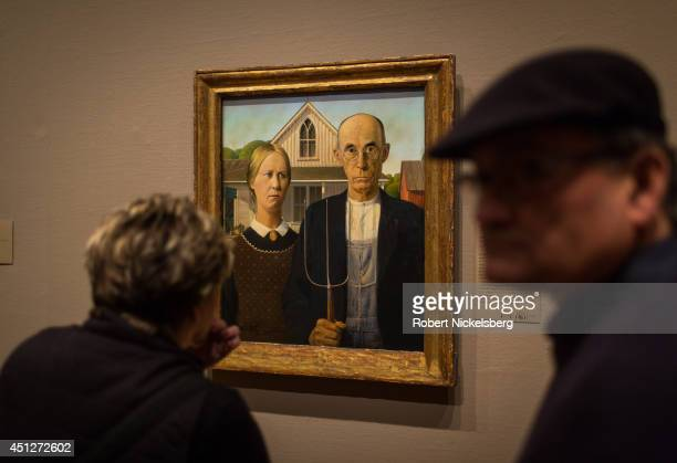Visitors to the Art Institute of Chicago view the painting American Gothic by Grant Wood January 15 2014 in Chicago Illinois