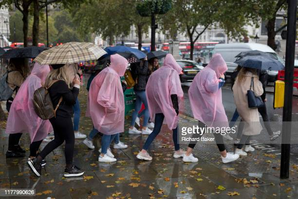 Visitors to the capital wearing identical plastic macs endure heavy rainfall on an autumn afternoon in Trafalgar Square, on 24th October 2019, in...
