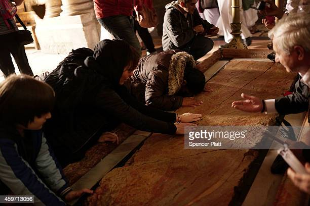 Visitors to the Church of the Holy Sepulchre kiss and touch the Stone of Anointing, where Jesus's body is said to have been anointed before burial on...