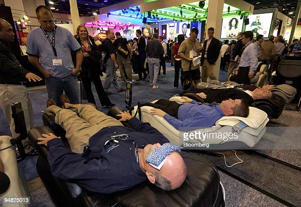 Visitors to the Consumer Electronics Show take a break from looking at products by trying out the iDeal Massage Chair Thursday January 5 2006 in Las...