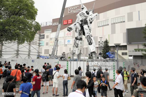 Visitors to the DiverCity Tokyo Plaza commercial complex take in the lifesize Unicorn Gundam statue under construction at Gundam Base Tokyo on August...