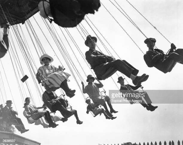 Visitors to the Hampstead Fair, London, enjoying a ride on the chair-swings.