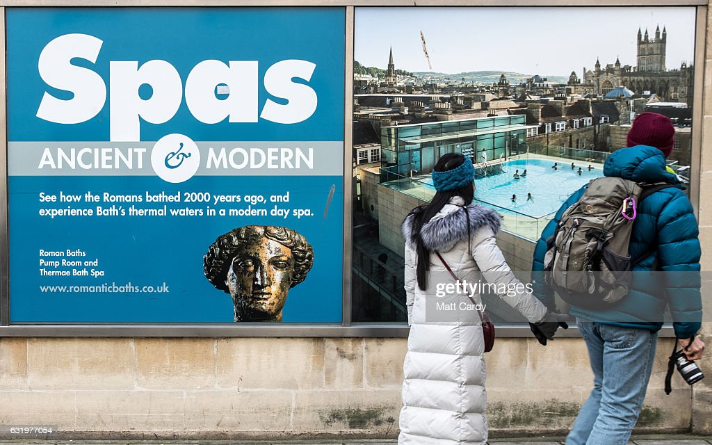 Visitors to the historic city of Bath stop to look a a poster advertising the Thermae Bath Spa (R) on January 18, 2017 in Bath, England. Plans for a possible overnight tourist bed tax are currently being discussed by Bath and North East Somerset council as one possible way of helping to bridge the £37million of cuts currently required by 2020. The city, a UNESCO World Heritage site, is famed for its Roman remains and Georgian architecture and attracts visitors from across the world.