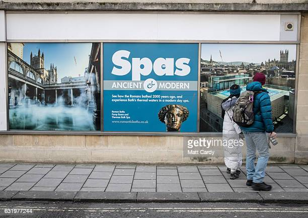 Visitors to the historic city of Bath stop to look a a poster advertising the Roman Baths Thermae Bath Spa on January 18 2017 in Bath England Plans...