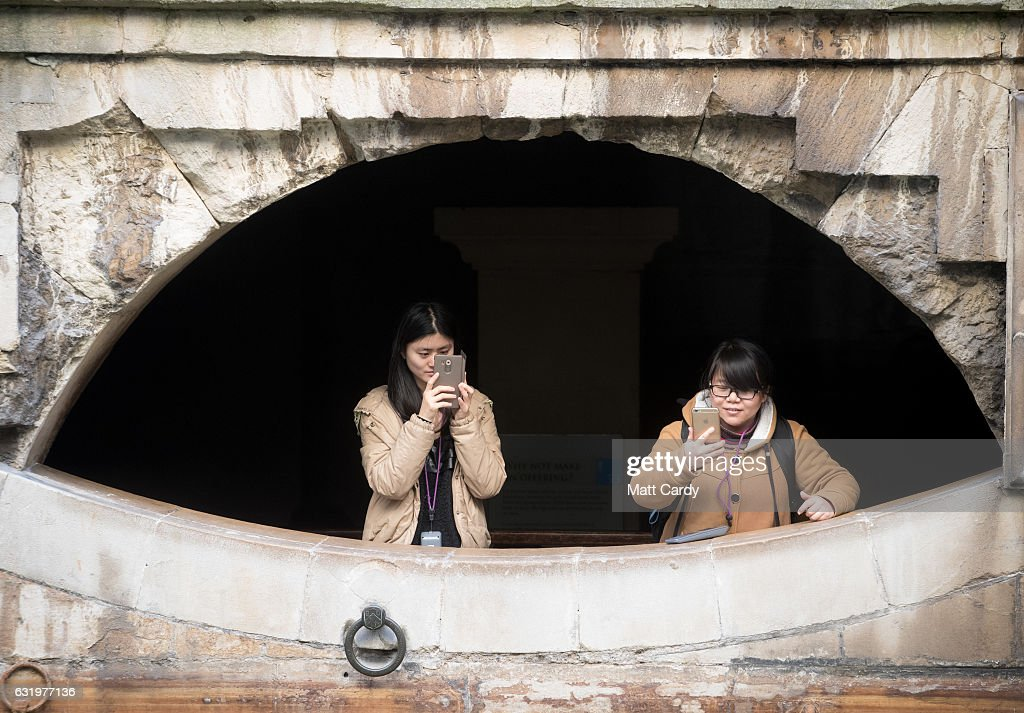 Visitors to the historic city of Bath take a photograph as they visit the Roman Baths on January 18, 2017 in Bath, England. Plans for a possible overnight tourist bed tax are currently being discussed by Bath and North East Somerset council as one possible way of helping to bridge the £37million of cuts currently required by 2020. The city, a UNESCO World Heritage site, is famed for its Roman remains and Georgian architecture and attracts visitors from across the world.