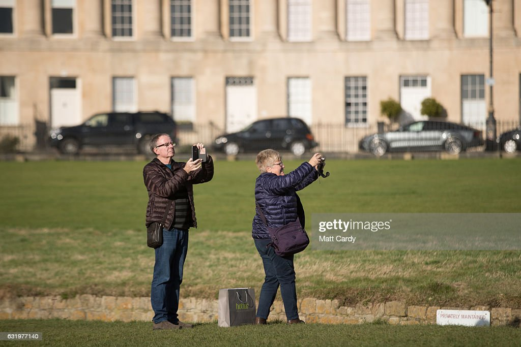 Visitors to the historic city of Bath take a photograph of the Royal Crescent on January 18, 2017 in Bath, England. Plans for a possible overnight tourist bed tax are currently being discussed by Bath and North East Somerset council as one possible way of helping to bridge the £37million of cuts currently required by 2020. The city, a UNESCO World Heritage site, is famed for its Roman remains and Georgian architecture and attracts visitors from across the world.
