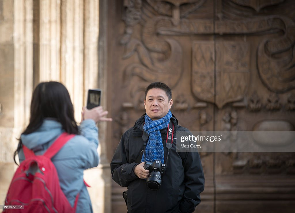 Visitors to the historic city of Bath take photographs in front of the Bath Abbey on January 18, 2017 in Bath, England. Plans for a possible overnight tourist bed tax are currently being discussed by Bath and North East Somerset council as one possible way of helping to bridge the £37million of cuts currently required by 2020. The city, a UNESCO World Heritage site, is famed for its Roman remains and Georgian architecture and attracts visitors from across the world.