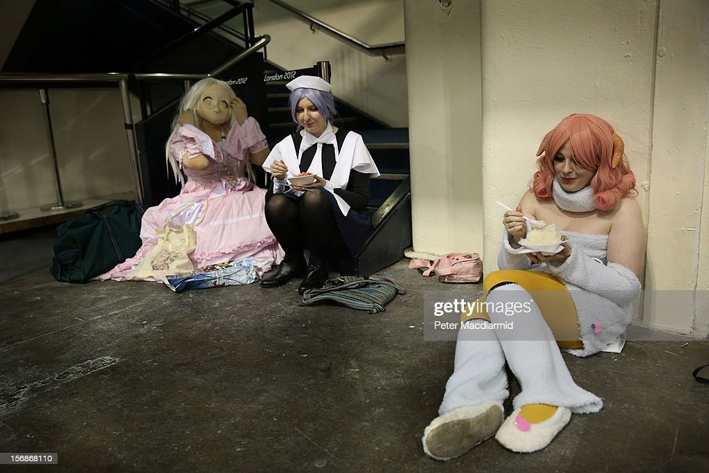 Visitors to The Hyper Japan event at Earls Court eat snacks dressed as characters on November 23, 2012 in London, England. The show is the UK's biggest Japanese Culture event, with stalls selling clothing and artwork. live music, Japanese food and computer gaming areas are also on show. Many attendees dress up as anime characters or in the lolita fashion widespread in Japan.