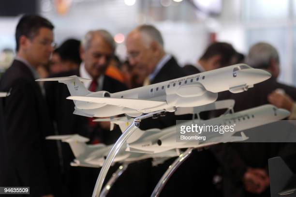 Visitors to the Latin America Aero Defense trade fair stand near Embraer aircraft models at the company's stand in Rio de Janeiro Brazil on Thursday...