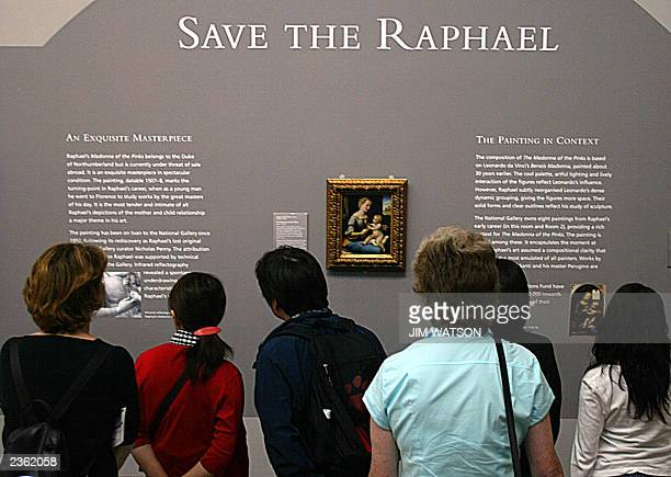 Visitors to the National Gallery in London look over Raphael's 'Madonna of the Pinks' 24 July 2003 which is in danger of being taken away from the...