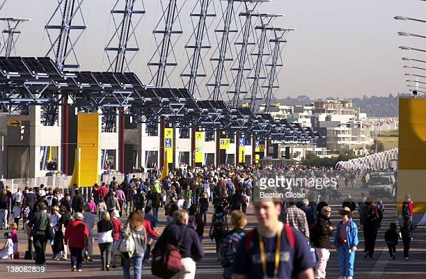 Visitors to the Olympic Games throng Olympic Boulevard on their way to the gymnastics venue to watch practice In the distance housing for athletes is...