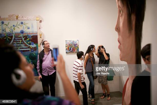 Visitors to the opening day of Art Basel look at a work by Evan Penny titled female stretch variation at the Miami Convention Center on December 5...