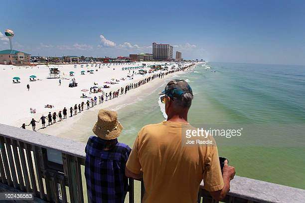 Visitors to the Pensacola pier look on as people stand together during a Hands Across The Sand event at the beach on June 26 2010 in Pensacola...