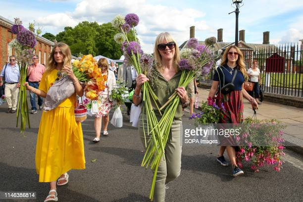 Visitors to the RHS Chelsea Flower Show seen carrying a wide variety of plants and flowers during the final day of the show. The Royal Horticultural...