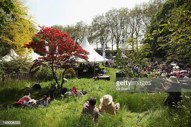 Visitors to the Royal Horticultural Society's Chelsea Flower Show relax in the shade in high temperatures on May 22 2012 in London England Britain is...