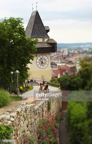 Visitors to the Schlossberg sit in front of the clock tower on May 29 2010 in Graz Austria Built in 1588 overlooking the city the bell tower has...