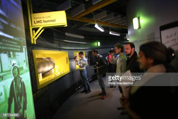 Visitors to the Science Museum stand in recretion of part of the Large Hadron Collider at the 'Collider' exhibition on November 12 2013 in London...