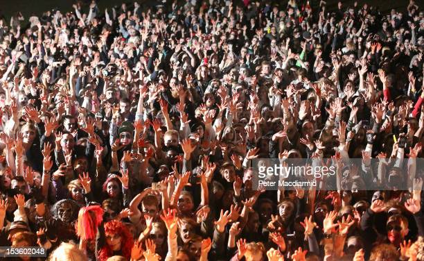 Visitors to the Shocktober Fest dressed as zombies raise their hands in unison at Tulleys Farm on October 6 2012 in Turners Hill England People...