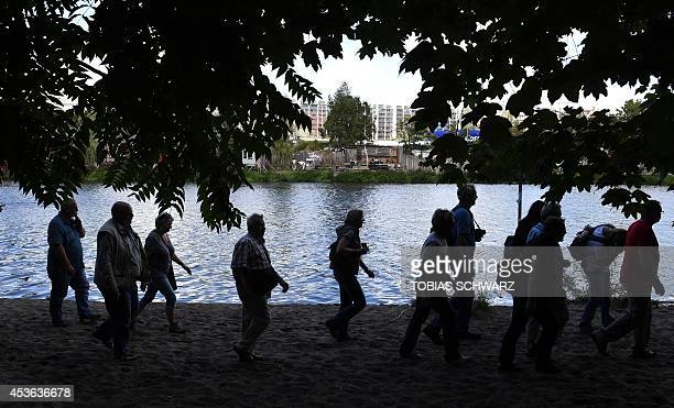 Visitors to the site of the former Berlin Wall border that used to separate WestBerlin and EastBerlin walk at a former East Germany's landing place...