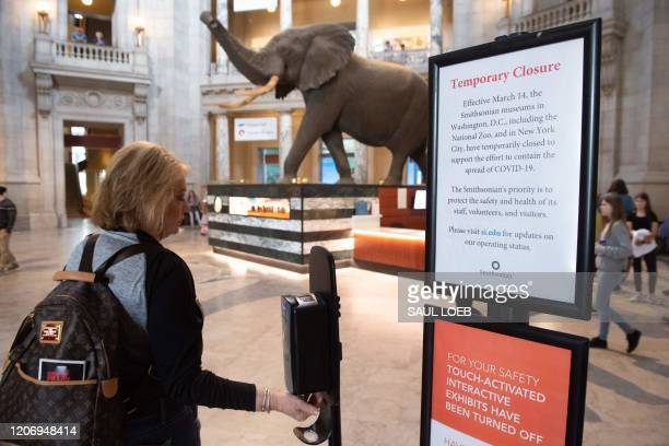 Visitors to the Smithsonian National Museum of Natural History use hand sanitizer as they arrive at the museum in Washington, DC, March 13, 2020. -...