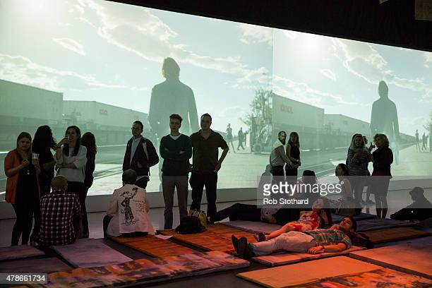 Visitors to the 'Station to Station A 30 Day Happening' opening party look at projections at Barbican Art Gallery on June 26 2015 in London England...
